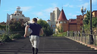 A young sporty guy quickly runs up the steps and rejoices at the top to his win. The man wears shorts and leggins, sport shoes, a T-shirt and an armband for phone. He is in the city with beautiful