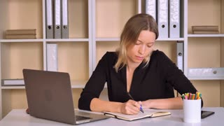 adult business woman working in modern office. beautiful caucasian employer sitting at the desk writing notes or planning day. attractive worker with blonde hair wearing elegant black dress