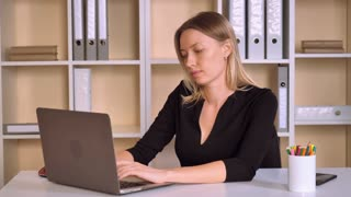 adult business woman working in modern office. beautiful caucasian employer working with computer looking on screen laptop with happy smile. attractive worker with blonde hair wearing elegant black