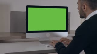adult businessman sitting at the working place at home or office typing on keyboard looking on green screen computer