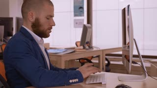 adult businessman wearing casual suit working in modern office. hipster with beard sitting at the working place in modern office chatting online or research something use internet