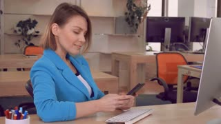 adult businesswoman using smartphone in bright casual office. candid manager wearing elegant suit chatting on smart phone scrolling touch screen. blonde entrepreneur at the workplace texting message