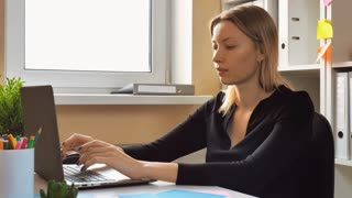 adult caucasian business woman working on computer turn to the camera and talking. employee telling viewers about her job with happy smile