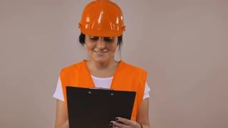 Adult caucasian woman wearing in hard hat and safety vest orange color working with documents . Portrait builder filling some form