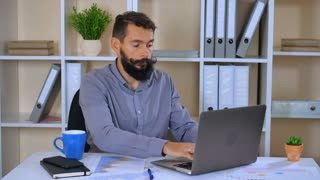 adult employer working in modern casual office. bearded business man sitting at the desk with laptop and different financial charts graphics and tables. entrepreneur entering data on computer