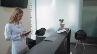 Adult man in dental clinic or in hospital standing in lobby talking with receptionist . Blonde woman greeting male using computer check patient admission time or make an appointment