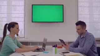 Adult man showing project on display with green screen his partner. Two coworkers looking on monitor. People sitting at working place in modern casual office