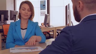 adult professional business woman explain about income growth. attractive caucasian worker looking on tables and diagrams talking with client.