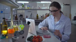 Adult professional woman make food quality test at working place. Woman holding petri dish. At the working place desk with laptop and vegetables