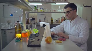 Adult reliable Lab technician entering results on computer doctor wearing in white coat working alone. professional caucasian man conducting food quality test at modern working place in