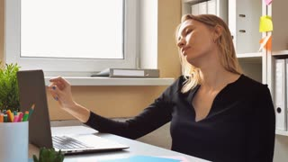 adult woman resting at the workspace. caucasian entrepreneur dancing in the small office. female with blond hair wearing black dress listening tranquil music sitting at the desk in room with window