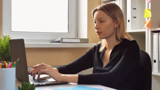 adult woman sitting at the desk in home office. caucasian lady with blonde hair using laptop surfing internet turn to the camera with cute friendly smile