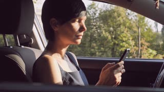 Adult woman sitting on the driver's seat in car holding smartphone messaging or chatting with friend. Brunette with short hair using internet for send email or texting message