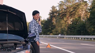 Adult woman standing near broken car on the roadside calling for help. Caucasian brunette wearing casual trendy dress travelling in summer evening