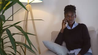 Adult woman talking by phone with boyfriend in living room with cozy interior in flat. Smiling girl sitting on sofa near floor lamp. Afro american model wearing in black trendy sweater