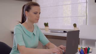 Adult woman typing fast on computer in office. Businesswoman sitting at the working place using laptop. Female with blond hair wearing in elegant casual dress works in room. Looking at the camera