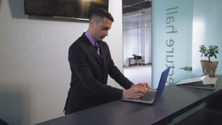 Adult worker standing at service desk using computer. Man wearing in suit looking on screen chatting online with client