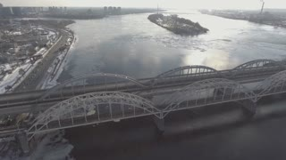 Aerial view city in spring season. Nature landscape with bridge over river. On the water float ice floes