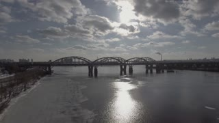 aerial view on the modern bridge over river. Spring season with snow on the coast. The sun's rays shine through the clouds