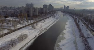 Aerial view on the town in eastern europe. Winter season in city. Urban landscape with different buildings modern and old river with shore in the snow