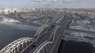 aerial view on the wither city kiev. Across the river bridge with driving cars. Snow in town ukraine country. Urban cityscape with buildings