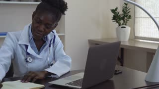African doctor at working place in clinic. Young professional physician handwriting on notebook. Afro american woman wearing in white coat sitting at the desk with computer