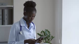 Afro american doctor reading medical record on digital touch screen tablet. Woman cardiologist wearing white coat standing in hospital