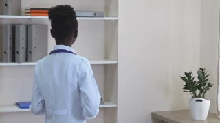 Afro american doctor standing in the office in hospital. slow motion. Young professional woman wearing in white coat holding digital tablet. Happy professional therapist with phonendoscope in clinic