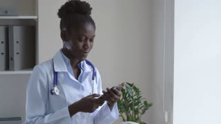 Afro american intern standing in clinic surfing internet on smartphone. Successful young woman looking at the camera. Lady wearing medical uniform white coat