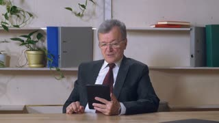 aged businessman has video conference call in office, elderly man sitting at the working place holding tablet and talking with partner or granddaughter. caucasian manager at work using application and