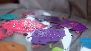 An artist uses putty knife to mix paints with water and oil. Process of combining violet color.
