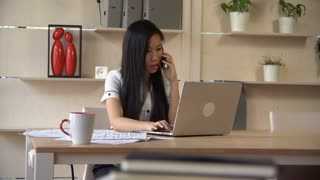 Asian designer talking on smartphone with client in the office. check information on computer
