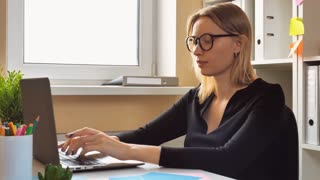 attractive adult business woman working on laptop sitting at the desk close her laptop looking at the camera friendly smiling. fashionable entrepreneur at work home office with window