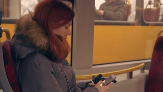 attractive female texting message on smart phone in public transport. beautiful girl with red long hair using smartphone messaging or use application mobile phone wearing winter jacket