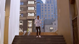 attractive girl jogging in urban city on background modern building cityscape sunlight