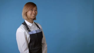 attractive korean woman with blond hair wearing white shirt and apron looking at the camera smiling. portrait young asian girl posing showing sign like on blue background in studio