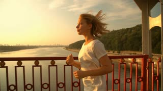 attractive lady is having a jogging. female runner runs above the river.