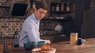 Bachelor preparing fast breakfast. Caucasian handsome man sitting at the table pouring pouring cereal into bowl. Guy wearing casual blue shirt in the morning in apartment