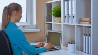 back view blonde woman using laptop. female wearing casual blue shirt sitting at workplace surfing internet entering data or works with document typing on computer