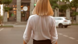 Back view elegant woman crosses the road in urban city. Female with blond hair walking on green traffic signal. slow motion