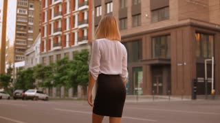 Back view elegant woman walking along the road in modern city. Girl wearing white shirt and black skirt going to work. slow motion