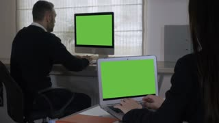 back view employees working in the office. businesswoman and businessman sitting at the working place typing on computer with green screen
