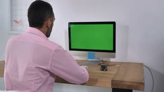 Back view man sitting at the desk with computer green screen. Male with black gray hair typing on keyboard entering data in room with white wall