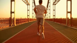back view of a male runner. guy wearing white t-shirt jogging along the bridge.
