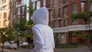 back view unrecognizable woman wearing hood running down the street. female in white hoodie runs near house in spring season