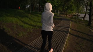 back view woman running at sunrise. fit female wearing bright sneakers and white hoodie run alone in park. beautiful nature landscape sunlight