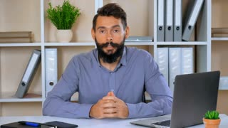 bearded businessman talking with viewers tell about his job. successful emotional employer sitting at the workspace looking at the camera emotionally gesticulates friendly smiling