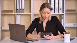 beautiful business woman using digital tablet sitting at the desk in modern office. happy worker scrolling touch screen watching funny photos and laughing