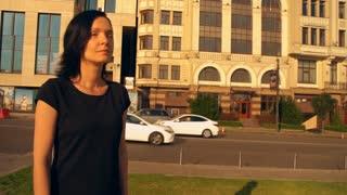 big city in the sunrise. brunette woman walking along busy street.