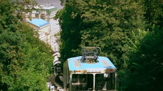 blue railway carriage goes down. amazing city landscape in the foot of the hill.